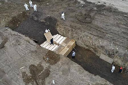 Arbeiter in Schutzanzügen vergraben schlichte Holzsärge in einem Graben auf Hart Island in der Bronx. Foto: John Minchillo/AP/dpa