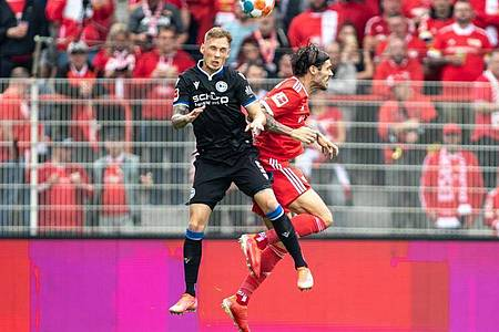 Jacob Barrett Laursen von Arminia Bielefeld springt gegen Berlins Christopher Trimmel (r) zum Kopfball. Foto: Andreas Gora/dpa