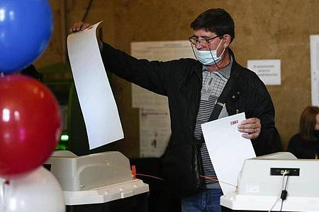 EinMann gibt in einem Wahllokal in Moskau seine Stimme ab. Foto: Alexander Zemlianichenko/AP/dpa