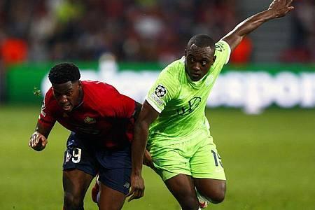 Jonathan David (l) vom OSC Lille gegen Kevin Mbabu vom VfL Wolfsburg. Foto: Michel Spingler/AP/dpa