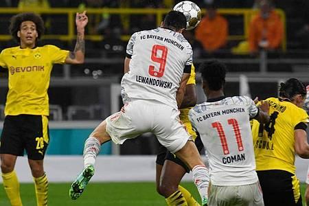 Bayern-Stürmer Robert Lewandowski (M) sorgt per Kopfball für die Führung in Dortmund. Foto: Bernd Thissen/dpa