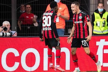 Leverkusens Jeremie Frimpong (l) und Torschütze Florian Wirtz jubeln nach dem Treffer zur 1:0-Führung. Foto: Marius Becker/dpa