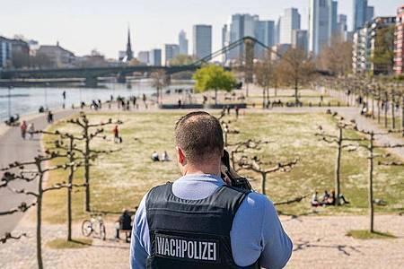Ein Wachpolizist überprüft die Einhaltung der Kontaktsperre am Frankfurter Mainufer. Foto: Frank Rumpenhorst/dpa