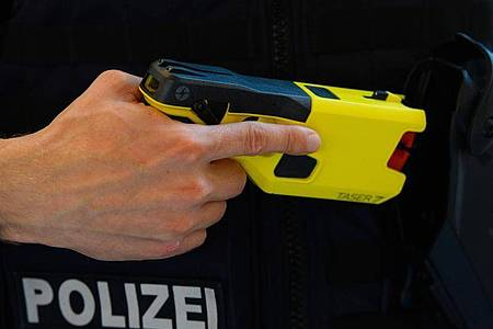 Ein Polizeibeamter präsentiert einen Taser. Foto: Soeren Stache/dpa-Zentralbild/dpa