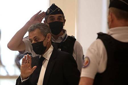 Nicolas Sarkozy (M) kommt am 15. Juni 2021 in einem Pariser Gerichtsgebäude an. Im Prozess gegen den früheren französischen Präsidenten wegen mutmaßlich überhöhter Wahlkampfkosten wird heute ein Urteil erwartet. Foto: Rafael Yaghobzadeh/AP/dpa