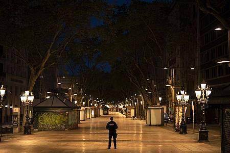 Ein katalanischer Polizist mitten auf der Straße La Rambla in Barcelona. In Spanien gilt eine landesweite Ausgangssperre. Foto: Felipe Dana/AP/dpa