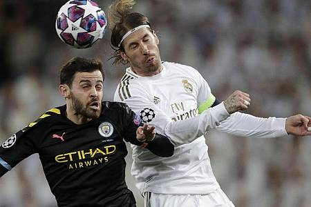 Bernardo Silva (l) von Manchester City und Sergio Ramos von Real Madrid im Kopfballduell. Foto: Bernat Armangue/AP/dpa
