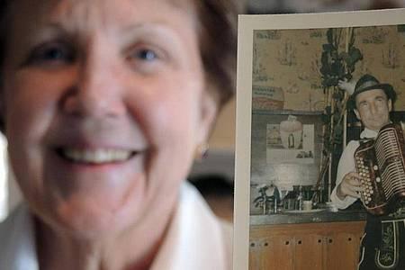 Celeste Sweeney zeigt ein Foto von einem Musikanten, das nach ihrer Erinnerung 1965 im Hofbräuhaus aufgenommen wurde. Foto: Benno Schwinghammer/dpa