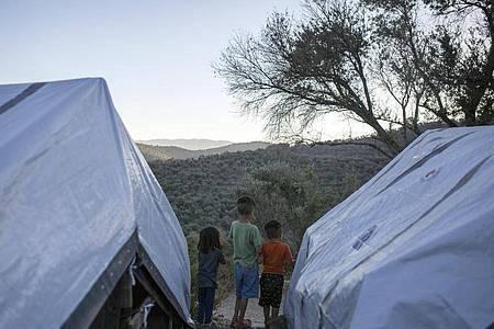 Kinder stehen zwischen Zelten in einem provisorischen Flüchtlingslager auf Lesbos. Foto: Socrates Baltagiannis/dpa