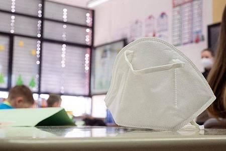 Eine FFP2-Maske liegt in einer ersten Klasse an einer Grundschule. Foto: Sebastian Gollnow/dpa