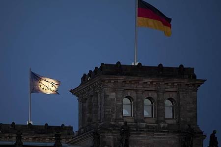 Der Mond geht hinter der EU-Flagge auf dem Reichstagsgebäude in Berlin auf. Deutschland übernimmt die Ratspräsidentschaft am 1. Juli von Kroatien für ein halbes Jahr. Foto: Christoph Soeder/dpa
