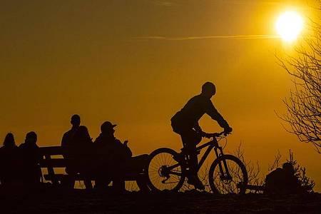 Ausflügler genießen den Sonnenuntergang auf dem Feldbergplateau im Taunus. Foto: Boris Roessler/dpa