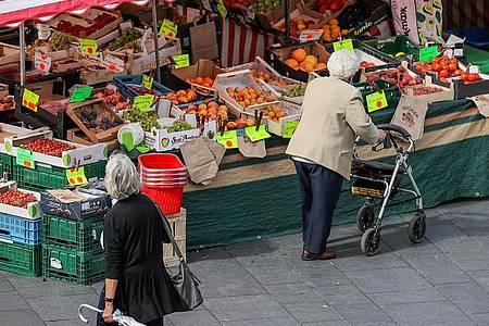 Eine Seniorin steht, gestützt auf ihren Rollator, vor einem Obst- und Gemüsestand auf dem Wochenmarkt. Foto: Jan Woitas/dpa-Zentralbild/dpa