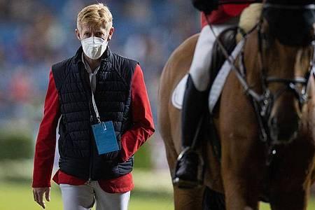 Der verletzte Reiter Marcus Ehning geht neben Daniel Deußer nach dessen Ritt aus dem Stadion. Foto: Rolf Vennenbernd/dpa