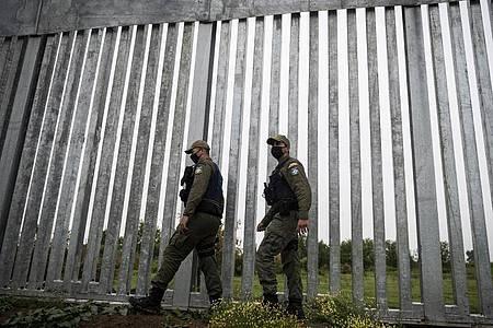 Polizeibeamte patrouillieren entlang eines Grenzzauns entlang der griechisch-türkischen Grenze. Foto: Giannis Papanikos/AP/dpa