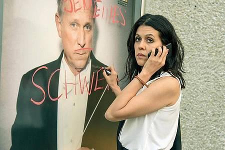 Ada (Daniela Golposhin) «verziert» ein Festspielplakat mit ihrem Kommentar zum Stardirigenten Marius Atterson (Ulrich Tukur). Foto: SWR/ORF/ARD/dpa