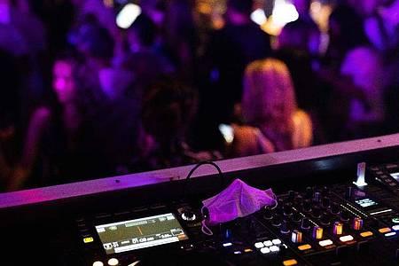 Eine Maske liegt auf einem Mischpult in einem Club. Foto: Philipp von Ditfurth/dpa