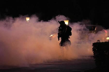 Ein Polizist geht durch Rauch während einer Demonstration gegen Corona-Impfungen in Ljubljana. Foto: Petr David Josek/AP/dpa