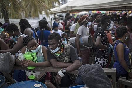 Haitianische Migranten warten darauf, an Bord eines Boots in Richtung Capurgana nahe der Grenze zu Panama zu gehen. Foto: Ivan Valencia/AP/dpa