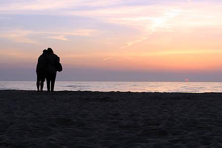 Paar guckt sich am Strand den Sonnenuntergang an