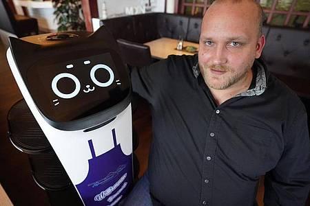 Gastwirt Tim Bornewasser in seinem Restaurant Hafenrestaurant mit seiner digitalen «Mitarbeiterin», dem Servierroboter ?Bella?. Foto: Marcus Brandt/dpa