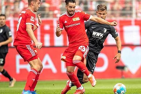 Unions Niko Gießelmann (M) im Laufduell mit dem Augsburger Florian Niederlechner (r). Foto: Andreas Gora/dpa