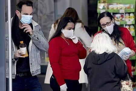 Die Mitarbeiterinnen eines Wiener Supermarktes verteilen am Eingang Mundschutzmasken an die Kunden. Foto: Ronald Zak/AP/dpa