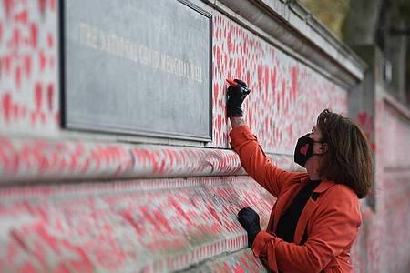 Eine Frau bei der Bemalung der Nationalen Covid-Gedenkmauer in London mit etwa 150.000 Herzen, zum Gedenken an die Menschen, die an den Folgen des Coronavirus gestorben sind. Foto: Victoria Jones/PA Wire/dpa