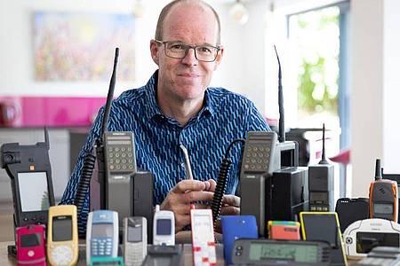 Auf dem vom Mobile Phone Museum herausgegebenen Foto sitzt Ben Wood, Gründer des Museums und Analyst des Unternehmens CCS Insight, hinter einigen der über 2.000 einzigartigen Mobiltelefone, die Teil des Online-Museums sein werden. Foto: Mobile Phone Museum/Vodafone/PA Media/dpa