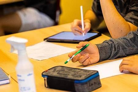 Ein Schüler hält beim Unterricht in seiner Klasse einen Stift, während ein anderer mit einem Tablet arbeitet. Foto: Philipp von Ditfurth/dpa