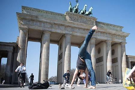 Menschen machen Yoga-Übungen vor dem Brandenburger Tor in Berlin. Foto: Jörg Carstensen/dpa