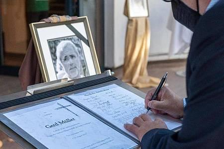 Ein Trauergast trägt sich in die Kondolenzliste zu Ehren Gerd Müllers ein. Foto: Stefan Puchner/dpa