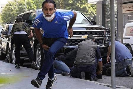 Schüsse der Sicherheitskräfte: Personen gehen hinter einem Auto in Deckung und versorgen einen verletzten Mann. Foto: Hassan Ammar/AP/dpa