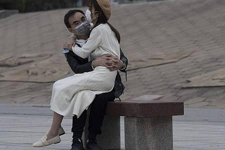 Ein Paar mit Mundschutz sitzt auf einer Bank im chinesischen Wuhan. In der Stadt, in der die Corona-Pandemie begann, fallen nach elf Wochen die letzten Bewegungsbeschränkungen für die elf Millionen Bewohner. Foto: Ng Han Guan/AP/dpa