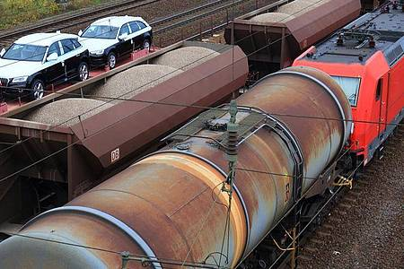 Eine Lokomotive zieht einen Güterzug mit Kesselwagen in Magdeburg (Sachsen-Anhalt) an einem Zug mit Autos und einem mit Schüttgut vorbei. Foto: Jens Wolf/dpa-Zentralbild/dpa