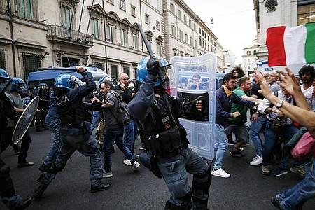 Polizisten setzen Schlagstöcke ein. Foto: Cecilia Fabiano/LaPresse/AP/dpa