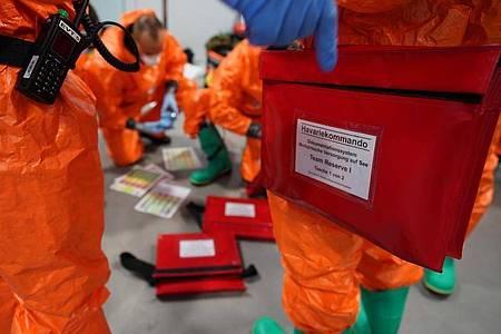 Einsatzkräfte des Havariekommandos bereiten sich während einer Großübung zur Vorbereitung auf Notfälle im Seuchenschutz im Hamburger Hafen auf ihren Einsatz vor. Foto: Marcus Brandt/dpa
