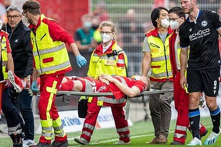 Berlins Timo Baumgartl wird nach einem Zusammenstoß mit Fabian Klos (r) von Arminia Bielefeld vom Spielfeld getragen. Foto: Andreas Gora/dpa