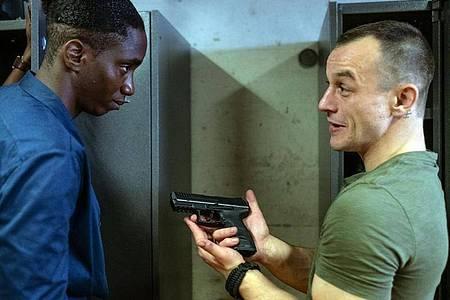 Mario (Paul Wollin, r) prahlt vor seinem Kollegen Man (Emmanuel Ajayi) mit seiner Pistole. Foto: Petro Domenigg/Filmstills.At K/ZDF/dpa
