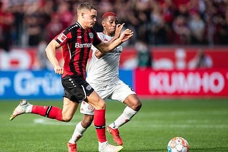 Leverkusens Florian Wirtz (l) und der Mainzer Leandro Barreiro laufen um den Ballbesitz. Foto: Marius Becker/dpa