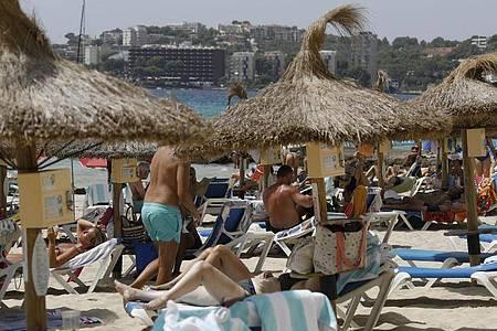 Einheimische und Touristen liegen am Strand Cala Major in Palma de Mallorca. Foto: Clara Margais/dpa