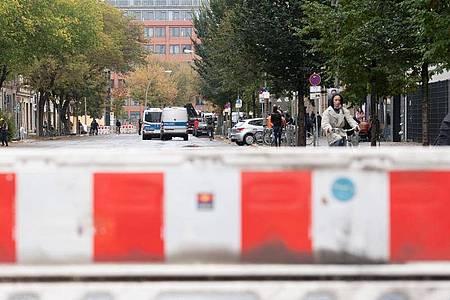 Absperrgitter und Einsatzfahrzeuge der Polizei stehen vor der geplanten Räumung der linken Bauwagensiedlung an der Köpenicker Straße. Foto: Paul Zinken/dpa