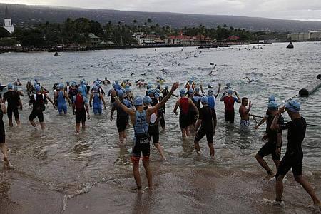 2019: Athleten stehen im Wasser der Kailia Bay für den Schwimmteil des Triathlons. Foto: Marco Garcia/FRE 132414 AP/dpa