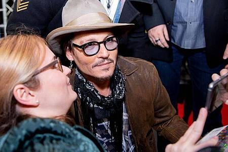 Johnny Depp posierte mit Fans für ein Foto. Foto: Christoph Soeder/dpa
