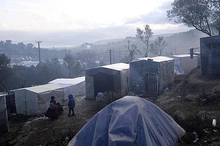 Kinder stehen nach einem Regenguss vor provisorisch errichteten Zelten außerhalb des Flüchtlingslagers Moria auf Lesbos. In und um die Registrierungslager harren mehr als 42.000 Menschen aus. Foto: Aggelos Barai/AP/dpa