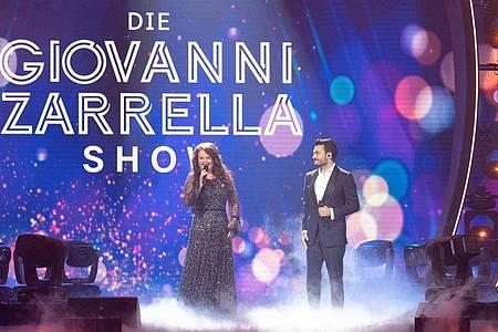 """Die britische Sopranistin Sarah Brightman und der Sänger Giovanni Zarrella stehen in der """"Giovanni Zarrella Show"""" gemeinsam auf der Bühne. Foto: Sascha Baumann/ZDF/dpa"""