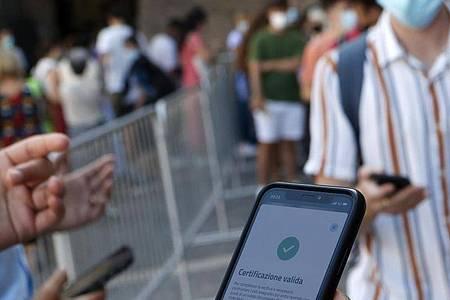 Ein Tourist zeigt am Eingang zu den Vatikanischen Museen seinen «Grünem Pass» vor. Ab jetzt müssen in Italien auch alle Beschäftigten in der Privatwirtschaft und im öffentlichen Bereich belegen, dass sie geimpft, genesen oder negativ getestet sind. Foto: Riccardo De Luca/AP/dpa