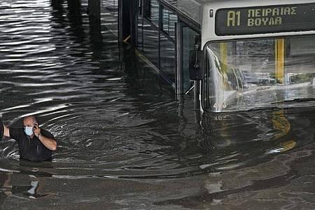 Ein Bus in Athen versinkt halb im Wasser. Foto: Thanassis Stavrakis/AP/dpa