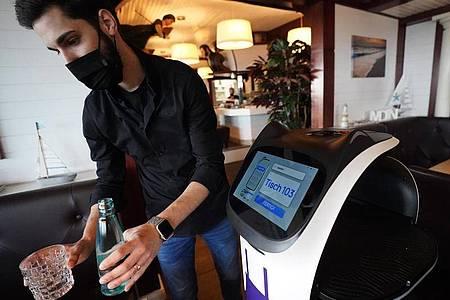 Ein Mitarbeiter serviert im Restaurant Hafenrestaurant mit Servierroboter ?Bella? an einem Tisch Getränke. Foto: Marcus Brandt/dpa
