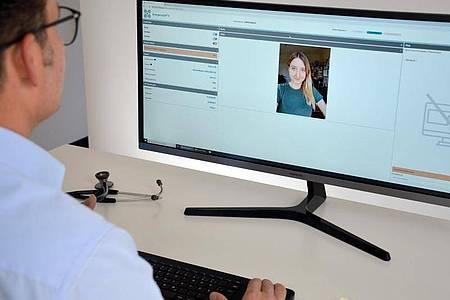 Ein Arzt (l.) im Gespräch mit einer Patientin im Live-Video-Chat über das System «EmergencyEye». Foto: -/Vodafone/dpa